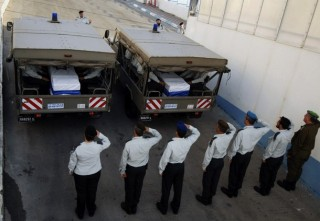 IDF officers salute the caskets of Goldwasser and Regev
